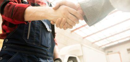 mechanik ściska dłoń klienta